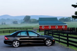 black car parked outside red house