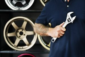 A man with tattoos on his arm holds a crescent wrench as he stands in front of a display of car wheel rims.