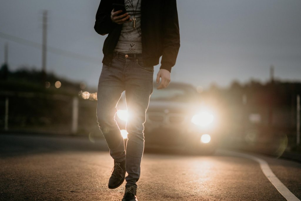 A man in jeans and a leather jacket walks in front of a car, back lit by bright HID headlights.