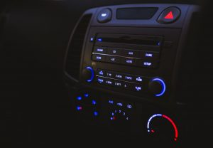 A car stereo system is gently lit by the glow of its own lights in a darkened car dashboard.