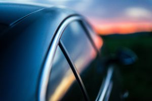 A dark car with tinted windows sits in the light of a glowing sunset.